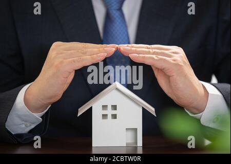 Businessman with house model on the desk. Real estate concept.