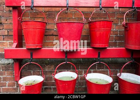 Close-up of period British Railways red fire buckets on Ropley Station, Mid-Hants Railway (the Watercress Line), Hampshire, England, UK