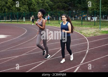 Fitness classes on the street. Lovely girlfriends run on the sports track at the stadium. Fit, athletic young women.