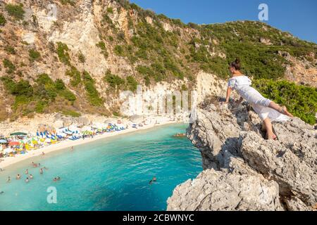 A girl in a white dress leans on a rocky ledge overlooking Agiofili Beach, Lefkada, Ionian Islands, Greece