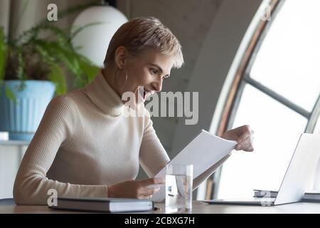 Surprised young short haired businesswoman reading paper documents.