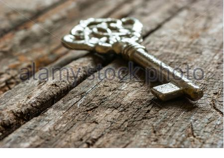 ancient, old metal key on chestnut rustic wooden background. Antique concept - Stock Photo