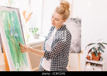 Female awesome artist painting picture, using spatula in workshop. close up side view photo. free time, spare time - Stock Photo