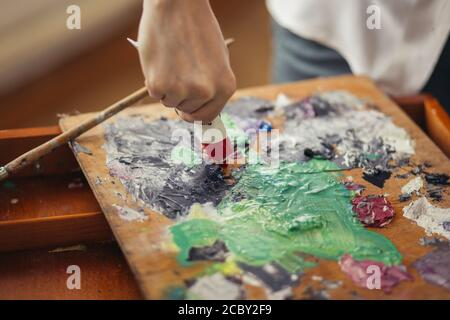 male artist holds acrylic paint tubes, mixes colors for painting on palette . Art, creativity, hobby concept. close up cropped photo - Stock Photo