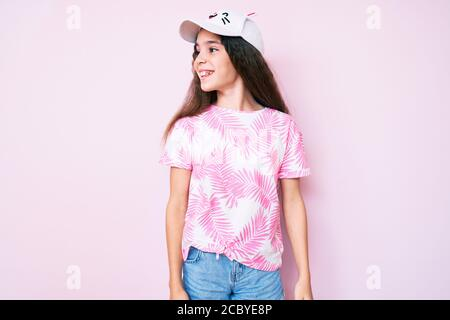 Cute hispanic child girl wearing casual clothes and funny kitty cap looking away to side with smile on face, natural expression. laughing confident. - Stock Photo