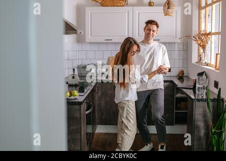 happy young caucasian married couple enjoy dancing at home in the kitchen, enjoy spending time together at weekends. couple in love, feelings, free ti - Stock Photo