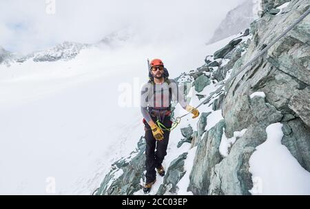 Male alpinist in sunglasses and safety helmet holding fixed rope while climbing snowy mountain. Mountaineer ascending natural rock formation. Concept of winter rock climbing.