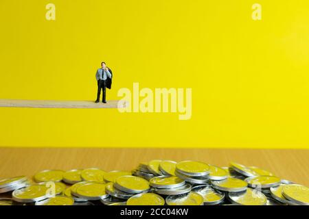 Miniature business concept - a businessman standing at the edge thinking strategy for financial risk management
