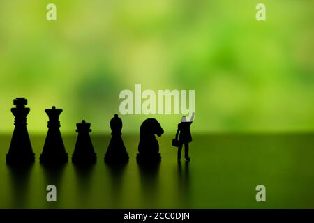 Business strategy conceptual photo - Silhouette of miniature businessman pointing upside, standing in front of chess piece row