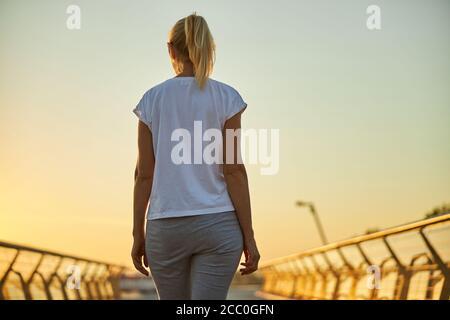 Blonde woman in white shirt standing on the bridge - Stock Photo