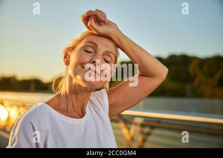 Beautiful serene woman placing hand on her forehead