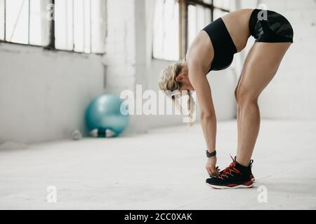 Muscular woman in sportswear with fitness tracker working out in gym