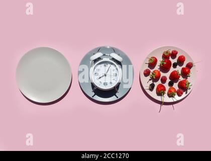 Intermittent fasting concept with empty colorful plates. On plate are berries, strawberries, raspberries, blackberries.Time to lose weight , eating