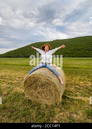 Redhaired woman riding hay haystack acting free person looking away aside - Stock Photo