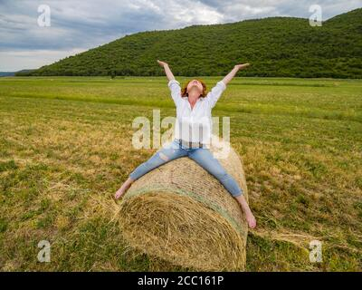 Redhaired woman riding hay haystack acting free person - Stock Photo