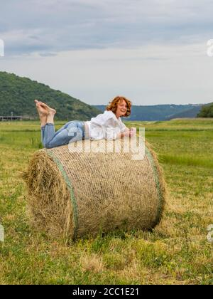 Redhaired woman on hay haystack leisure lazy - Stock Photo