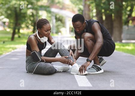 Jogging Injuries. Black Guy Helping Girlfriend Suffering From Sprained Ankle After Running