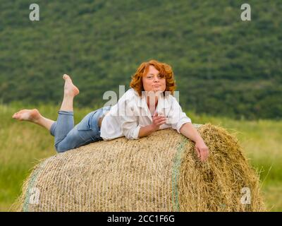 Redhaired woman on hay haystack leisure - Stock Photo