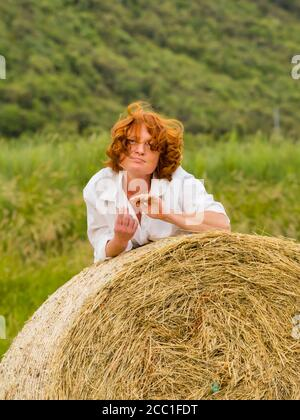 Redhaired woman on hay haystack portrait view - Stock Photo