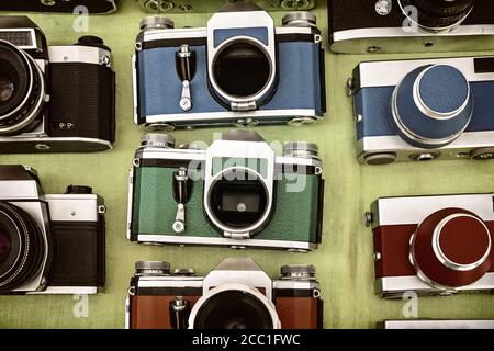 Retro styled image of colorful photo cameras on a flee market