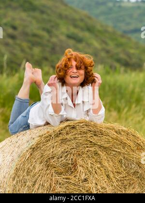 Redhaired woman on hay haystack - Stock Photo