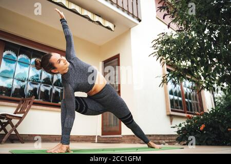 Full length of healthy young woman in sportswear doing stretching exercise at patio