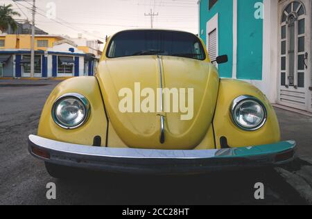 Merida, Yucatan, Mexico - 20 November 2018: Old yellow Volkswagen beetle in the colonial streets during sunset - Stock Photo