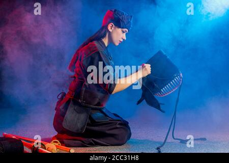 cuacasian kendo female wearing protective helmet on head before practicing fight. traditional japanese martial arts concept
