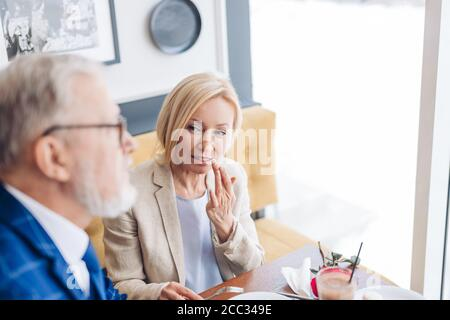 attractive elegant woman showing her husband to show his mouth after eating cake. close up photo - Stock Photo
