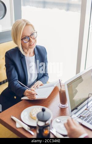 smiling happy young woman in trendy blue suit listening to her partner and writing with a pen. close up photo. freelancer