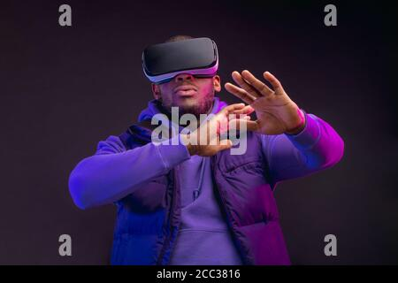 Young dark-skinned man dressed in outdoor wear having on head mobile virtual reality headset for playing 3D game but Mankind meets a new era of contro