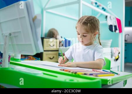 Portrait of a cute little girl looking at the camera and smiling while drawing pictures or doing homework, sitting at a table in the home interior