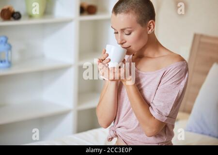 Young beautiful girl with short hair sit on bed in light room and enjoy drinking tea or coffee at morning at home.