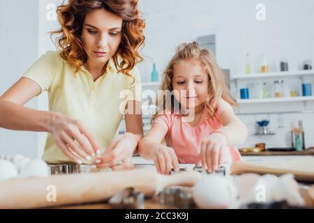 selective focus of curly mother and blonde daughter preparing cookies in kitchen together