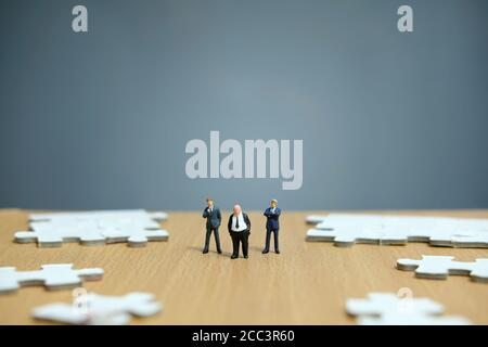 Conceptual photos of business strategies - miniature people businessmen standing in front of uncomplete jigsaw puzzles - Stock Photo