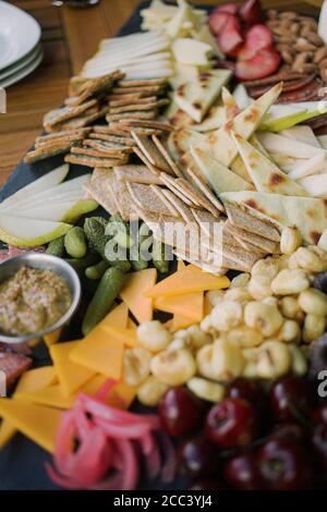 Charcuterie Board with cheese, fruit and pickles - Stock Photo
