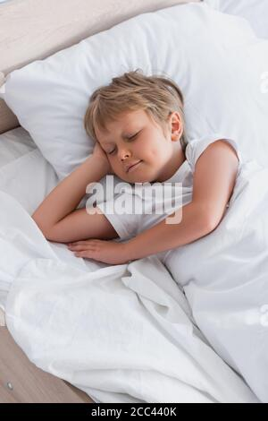top view of boy sleeping on white bedding in morning Stock Photo