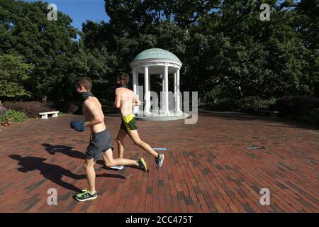 Chapel Hill, North Carolina, USA. 18th Aug, 2020. Two runners jog past the iconic Old Well on the campus of UNC-Chapel Hill. The school will move all undergraduate classes online starting Wednesday, after 130 more students tested positive for the coronavirus. There have been reports of four COVID-19 clusters over three days in dorms, apartments and a fraternity house. Credit: Bob Karp/ZUMA Wire/Alamy Live News - Stock Photo