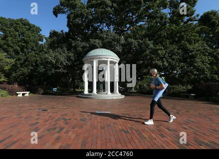 Chapel Hill, North Carolina, USA. 18th Aug, 2020. Freshman MARIA SMITH of Denton, NC walks past the iconic Old Well on the campus of UNC-Chapel Hill. The school will move all undergraduate classes online starting Wednesday, after 130 more students tested positive for the coronavirus. There have been reports of four COVID-19 clusters over three days in dorms, apartments and a fraternity house. Credit: Bob Karp/ZUMA Wire/Alamy Live News - Stock Photo