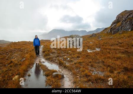 A person walking in Scottish countryside near the Allt Coire Rooill river in Torridon, Scotland