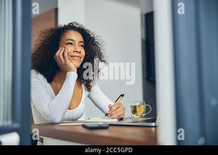 Beautiful African American woman dreaming with pen in hands - Stock Photo