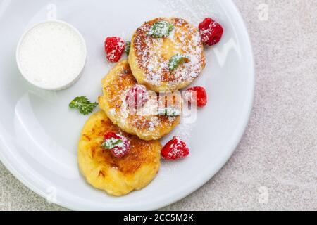 Beautiful morning breakfast: cheesecakes with raspberries