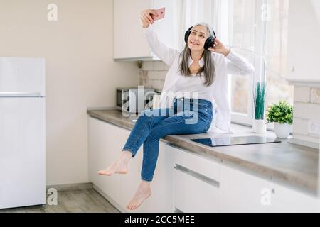 People at home concept. Happy Caucasian elderly woman with headphones holding mobile phone for making photo or video call, while sitting on kitchen