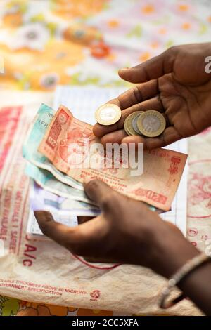 Cash Indian Rupees are counted at a women's village savings and loan group in Bihar, India. - Stock Photo