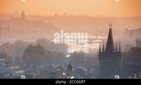 Panorama of Prague with the gothic tower of Charles bridge and the silhouettes of bridges over the river Vltava (Moldau), Czech Republic - Stock Photo
