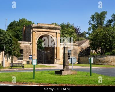 Rudding Gates former entrance to Rudding Park Estate and Saxon Cross on the village green in Follifoot near Harrogate North Yorkshire England - Stock Photo