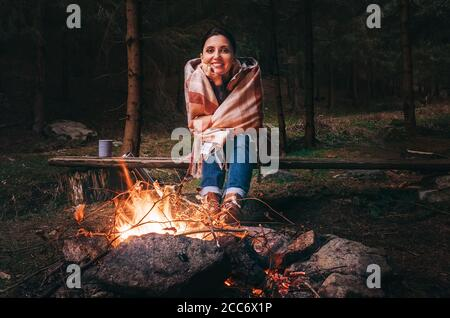 Pretty smiling young woman sits near the campfire in twilight autumn forest
