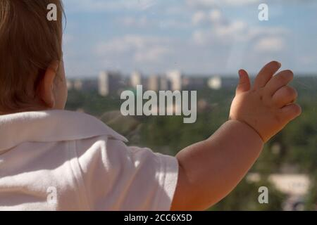 Rear view baby boy looks out through window and shows with hand outward, selective focus - Stock Photo