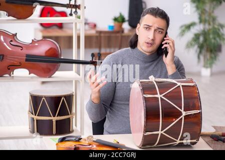 Young male repairman repairing drum in workshop - Stock Photo