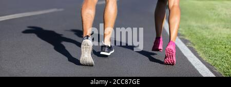Fitness runners running road to weight loss banner - couple of young people jogging together - crop of legs and running shoes - Stock Photo